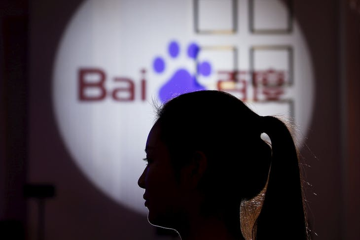 A woman is silhouetted against the Baidu logo at a new product launch from Baidu, in Shanghai, China, November 26, 2015. Thousands of apps running code built by Chinese Internet giant Baidu have collected and transmitted users' personal information to the company, much of it easily intercepted, researchers say. Picture taken November 26. REUTERS/Aly Song - RTX28A21