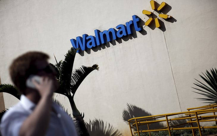 A man talks on his mobile phone in front of a Wal-Mart store in Sao Paulo, Brazil, February 16, 2016. To match Insight WALMART-BRAZIL/   REUTERS/Nacho Doce  - RTX27ANW
