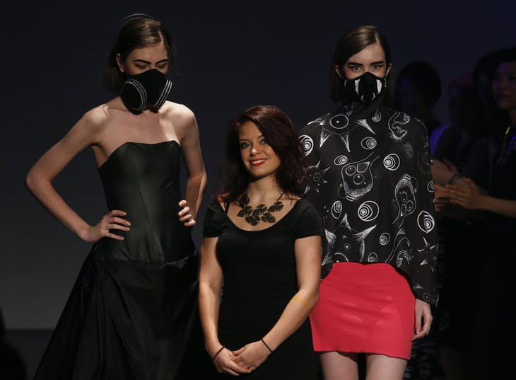 Hong Kong and Beijing based British designer Nina Griffee (C) acknowledges the audience with models wearing designer Vogmasks that provides protection from PM 2.5 particles at the Hong Kong Fashion Week for Spring and Summer 2015, in Hong Kong July 8, 2014. REUTERS/Bobby Yip (CHINA - Tags: ENVIRONMENT FASHION) - RTR3XJQJ