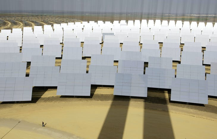 A man walks next to solar panels (bottom L) at a soon-to-be completed solucar solar park at Sanlucar La Mayor, near Seville, February 13, 2008. The first of two solar thermal power plants uses mirrors to concentrate the sun's rays onto the top of a 100 metre (300 foot) tower where it produces steam to drive a turbine. The lines in the photograph are due to reflections on the solar panels. REUTERS/Marcelo del Pozo (SPAIN) - GM1DXGISCDAA