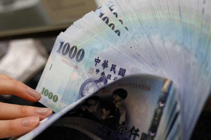 A teller counts New Taiwan dollar (TWD) $1000 banknotes at a bank in Taipei, Taiwan February 23, 2017.  Picture taken February 23, 2017. REUTERS/Tyrone Siu - RC1A137D3F40